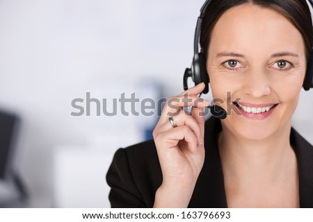 Friendly smiling receptionist, personal assistant or call centre operator , head and shoulders close up portrait with copyspace