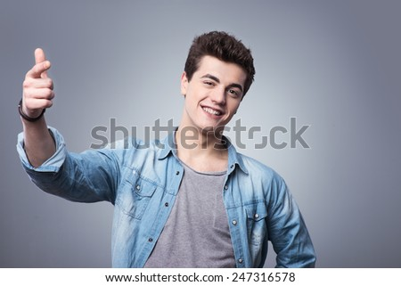 Friendly smiling teenager in casual wear having fun and gesturing - stock photo