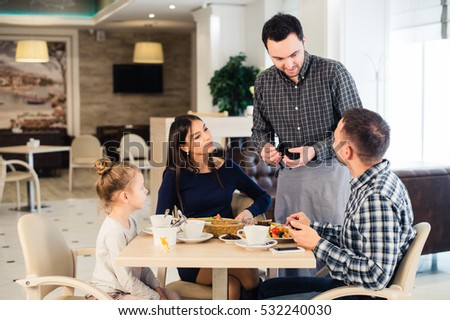 Friendly smiling waiter taking order at table of family having dinner together