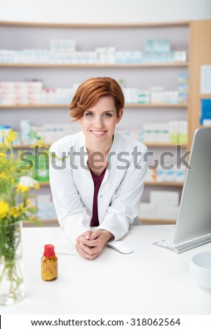 Friendly smiling young woman pharmacist leaning on the counter in the pharmacy with a bottle of pills in front of her smiling at the camera - stock photo