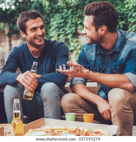 Friendly talk. Three happy young people drinking beer and talking to each other while sitting outdoors - stock photo