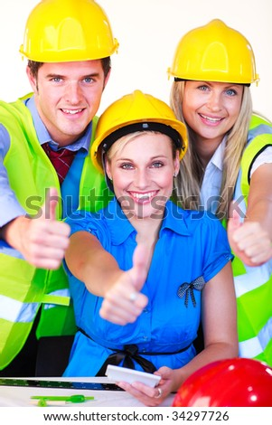 Friendly team with hard hats looking at the camera with thumbs up - stock photo