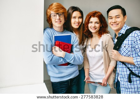 Friendly teenagers looking at camera in college - stock photo