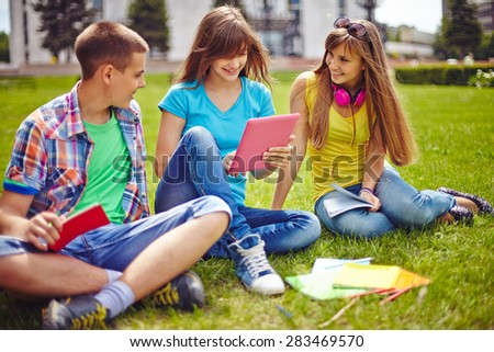 Friendly teenagers sitting on green lawn at leisure - stock photo