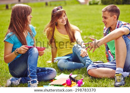 Friendly teenagers spending free time on green lawn - stock photo
