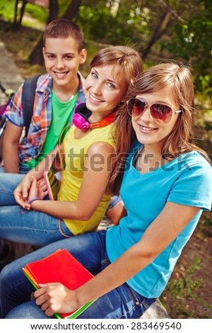 Friendly teens resting in park after lessons - stock photo