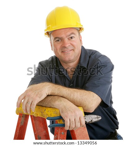Friendly, typical construction worker on top of a ladder holding a pliers.  Isolated on white. - stock photo