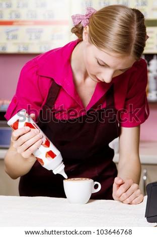 Friendly waitress making coffee at coffee machine - stock photo