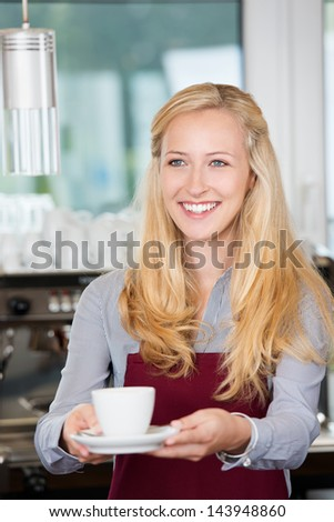 friendly waitress passing a cup of coffee over the counter - stock photo