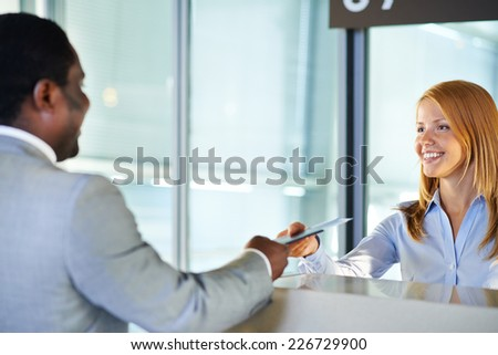 Friendly woman giving passport and ticket back to businessman at airport check-in counter - stock photo