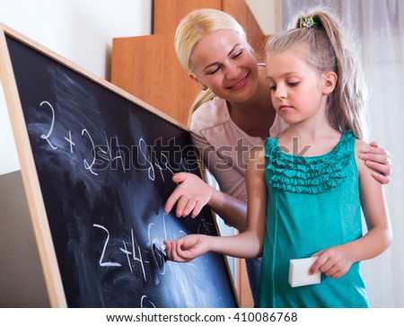Friendly woman introducing numbers to small girl at home