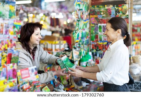 friendly woman selling seeds to mature buyer in store