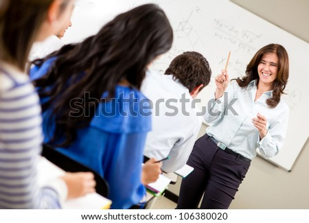 Friendly woman teaching a class and smiling - stock photo