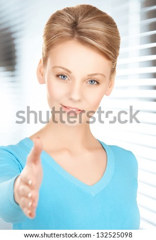 friendly woman with an open hand ready for handshake - stock photo