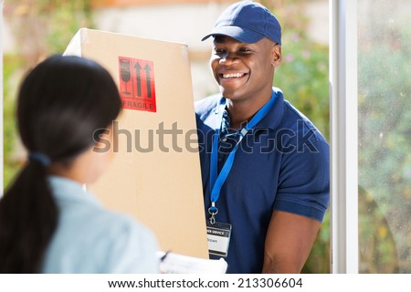 friendly young african american delivery man delivering a package - stock photo