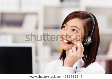 Friendly young Asian call centre operator chatting on the headset phone and smiling as she listens to the customer speaking as she tries to assist