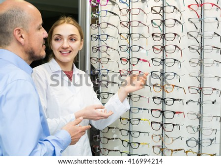 Friendly young female optician offering glasses frames to mature male customer