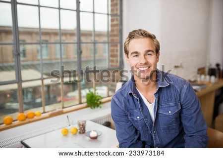 Friendly young man with a lovely smile sitting in his kitchen in his urban apartment in front of the window looking at the camera - stock photo
