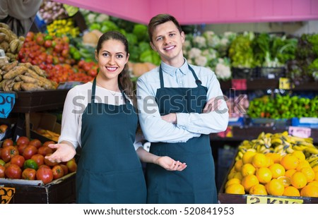 Friendly young sellers having vegetables and fruits on displays of market