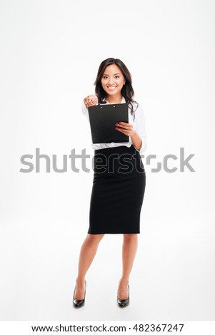 Friendly young smiling asian businesswoman with clipboard pointing pencil at camera isolated on white background