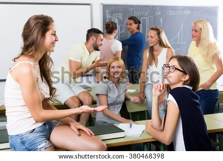 Friendly young students chatting while sitting in the room. Focus on the right woman - stock photo