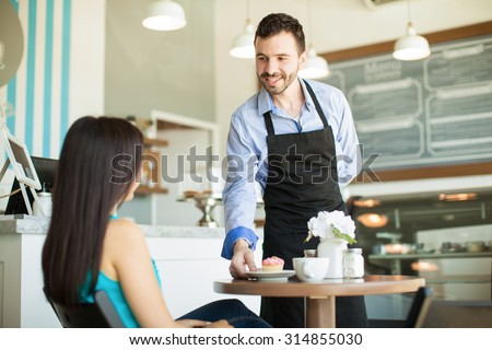 Friendly young waiter serving a cupcake and some coffee to one of his customers in a cake shop - stock photo