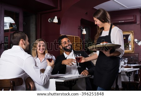 Friendly young waitress serving meal for guests at table in restaurant  - stock photo