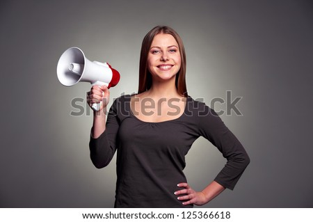friendly young woman holding megaphone and smiling. studio shot over dark background - stock photo