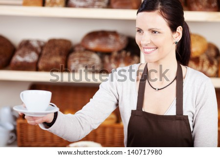 Friendly young woman in an apron serving a hot cup of coffee in a bakery against a backdrop of specialist loaves of bread - stock photo