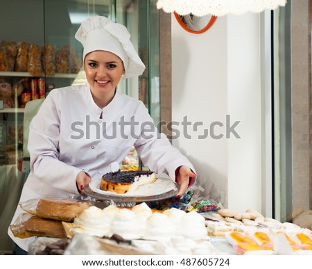 Friendly young woman with cook hat posing in bakery near pastry