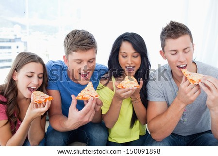 Friends about to take the first bite of their pizza slices - stock photo