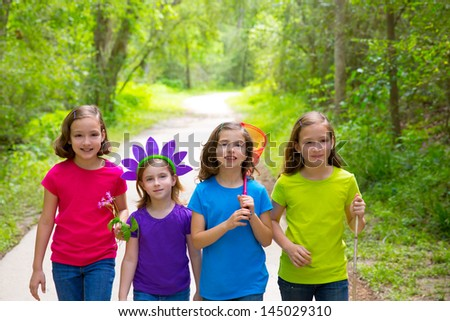 Friends and sister girls walking outdoor in forest track excursion - stock photo