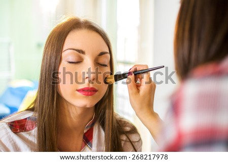 Friends applying makeup at home. - stock photo