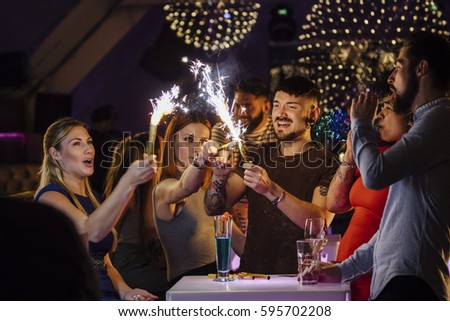 Friends are celebrating together in a nightclub. They are lighting indoor sparklers while dancing.