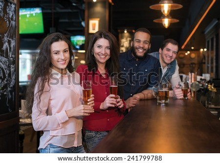 Friends are drinking beer. Four friends are having fun in a pub and drinking beer - stock photo