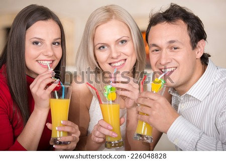 Friends are drinking juice in the pizzeria. Close-up. - stock photo