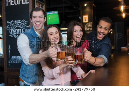 Friends are having fun with beer. Four best friends are standing in a pub and drinking beer with smiles - stock photo