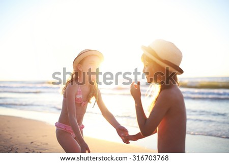 friends are playing on the beach during sunset - stock photo