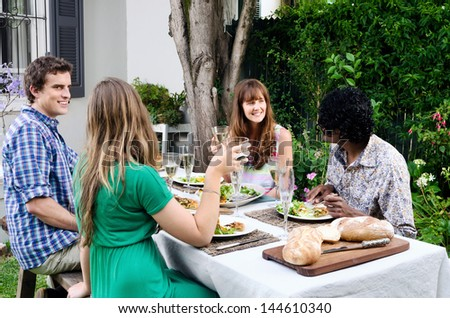 Friends at a party talking over food and wine - stock photo