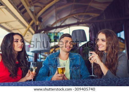 Friends at party drinking cocktails and having fun - Three tourists drinking aperitif in a restaurant - stock photo