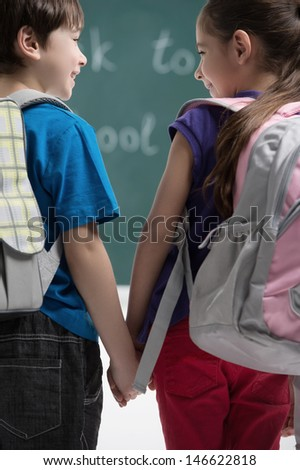 Friends at school class. Rear view of classmates holding hands and smiling to each other - stock photo