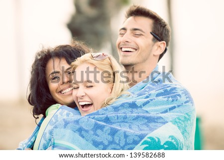 Friends at Sunset on the Beach in California wrapped in a towel together - stock photo