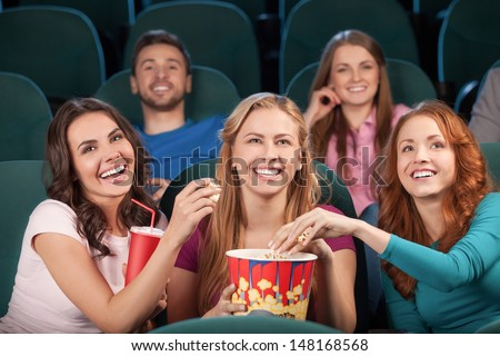 Friends at the cinema. Happy young people watching movie at the cinema and laughing - stock photo