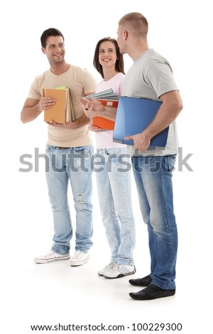 Friends at university standing talking to each other, holding books and notes, smiling happily, isolated on white. - stock photo