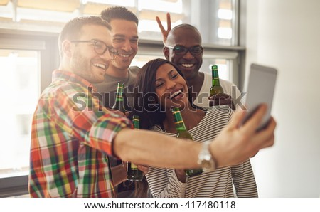 Friends at work taking self portrait with camera phone while holding green glass bottles of beer in office party - stock photo