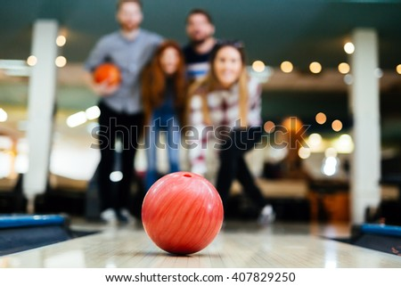 Friends bowling at club and having fun playing casually - stock photo