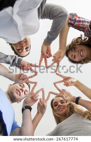 Friends build a star by holding together their fingers
