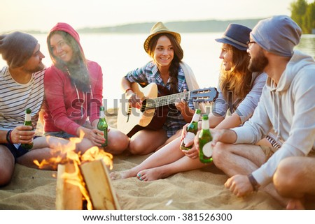 Friends by camp fire - stock photo
