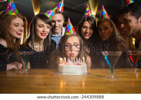 Friends celebrating a birthday together in a bar - stock photo