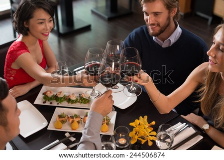 Friends celebrating life event in a restaurant - stock photo